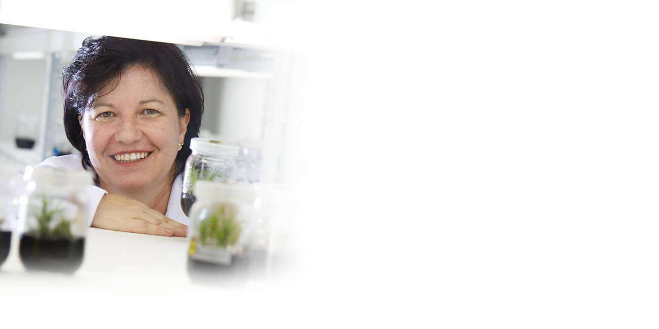 Woman in lab coat posing with plants in jars
