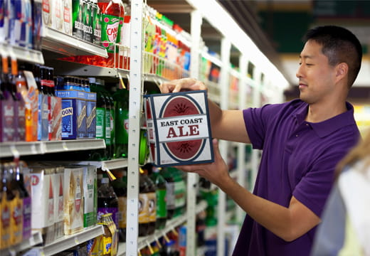 A man in a grocery store looking at a case of beer