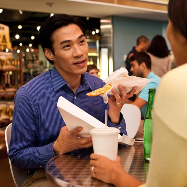 A man eating a slice of pizza out of a to-go box