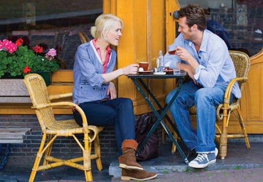 Two people sitting outside drinking coffee