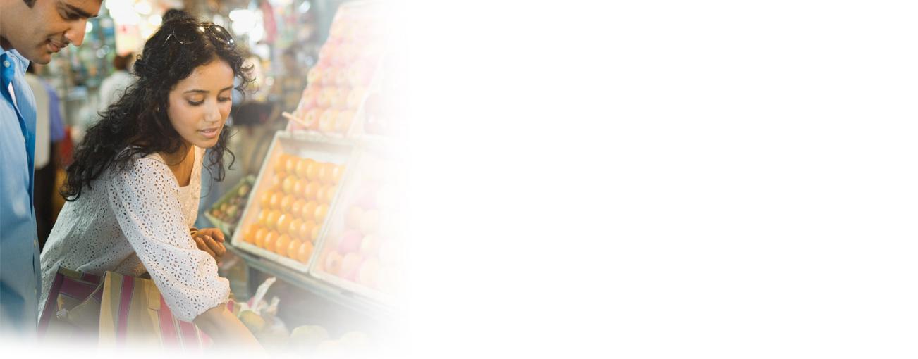 Um homem e uma mulher comprando frutas em um mercado