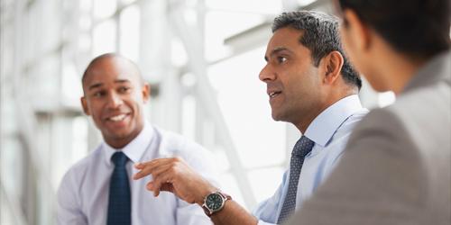 Três homens em uma reunião discutindo o trabalho.