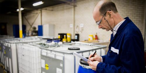 Um homem inspecionando caixas de fabricação.