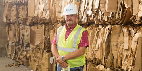 A man in a vest and hard hat standing in front of recycled fiber paperboard.