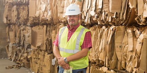 Um homem de colete e capacete em pé diante de papelão de fibra reciclado.
