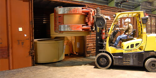 A forklift loading a roll of paperboard into a shipping crate.