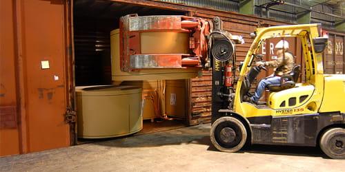 Uma empilhadeira carregando um rolo de papelão em uma caixa de transporte.