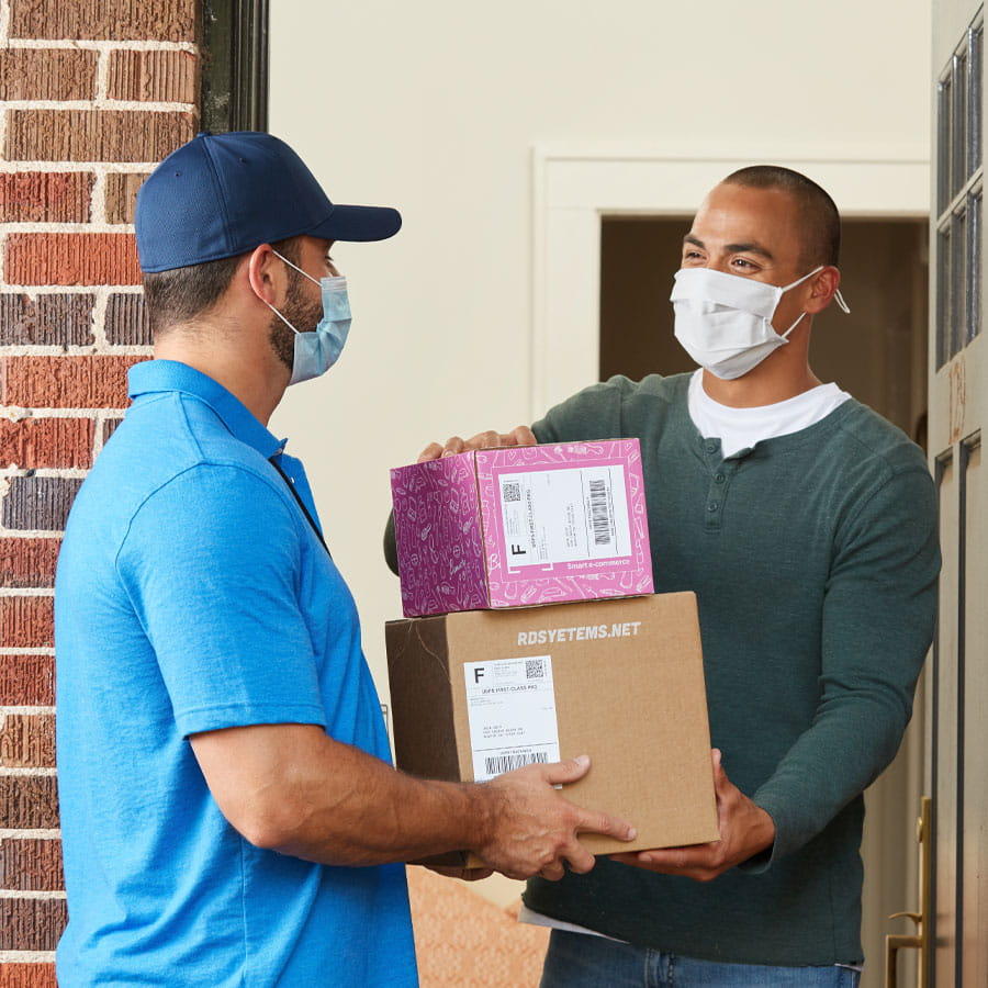 Man receiving packages at front door from deliveryman