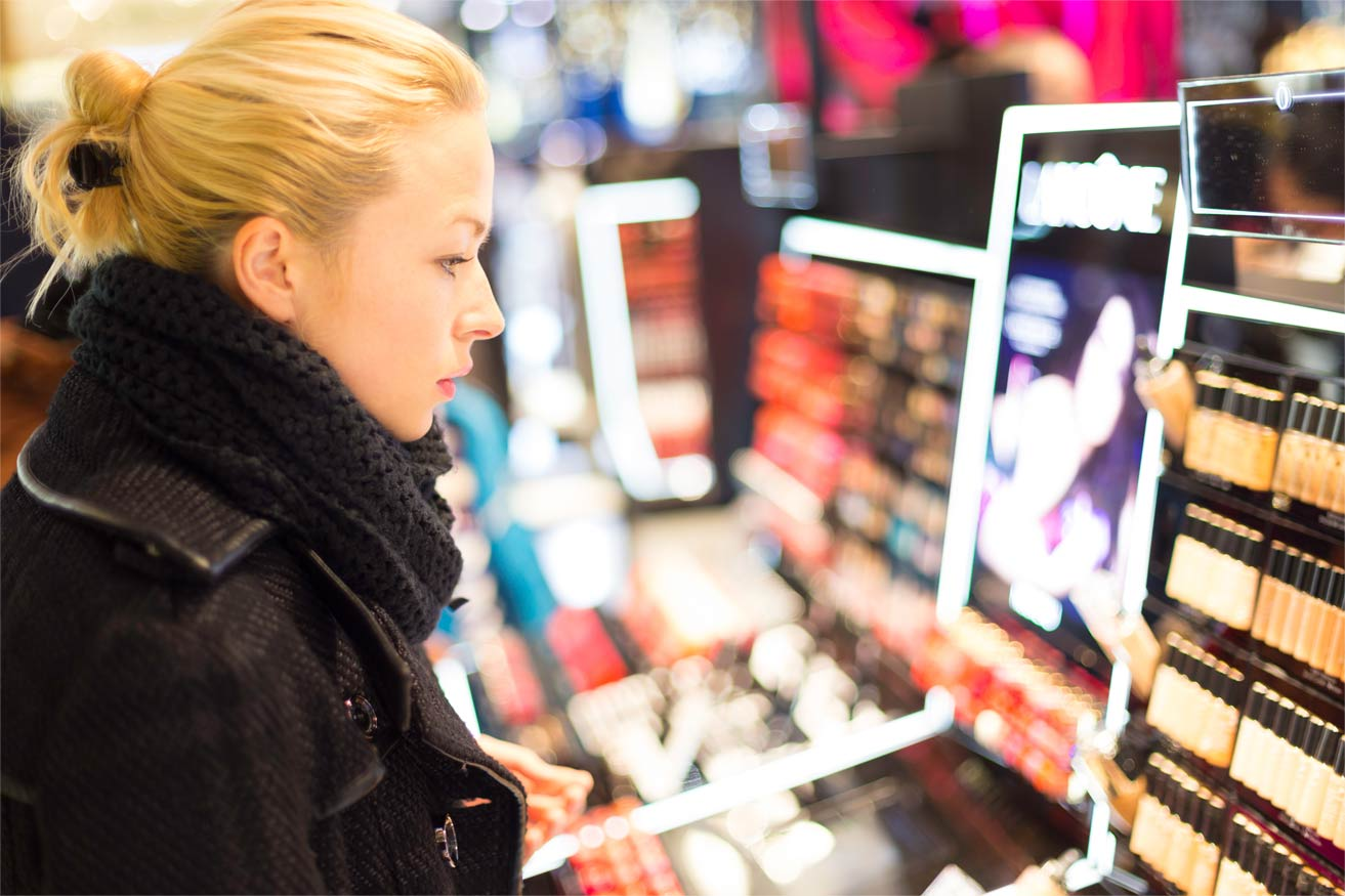 A woman standing in a retail aisle looking at beauty makeup.