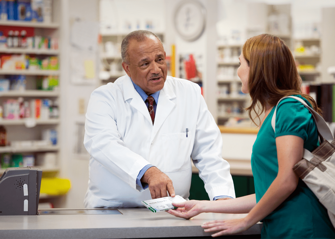 A pharmacist talking to a customer in a pharmacy.