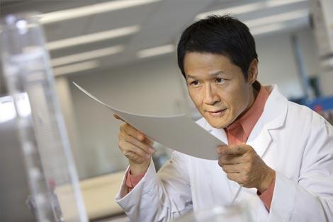 Homem em um laboratório olhando para uma folha de papel.