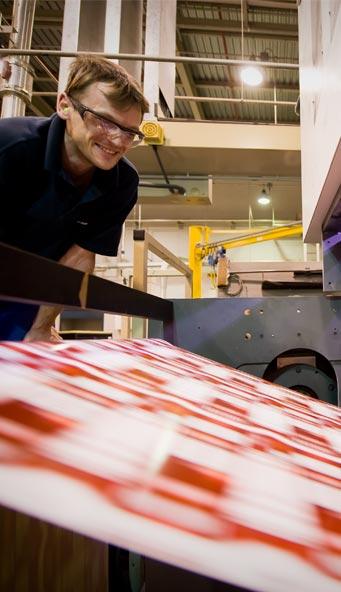 Homem na fábrica olhando para uma bobina de papel