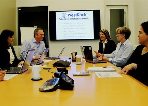 Um grupo de funcionários em uma mesa de reunião.