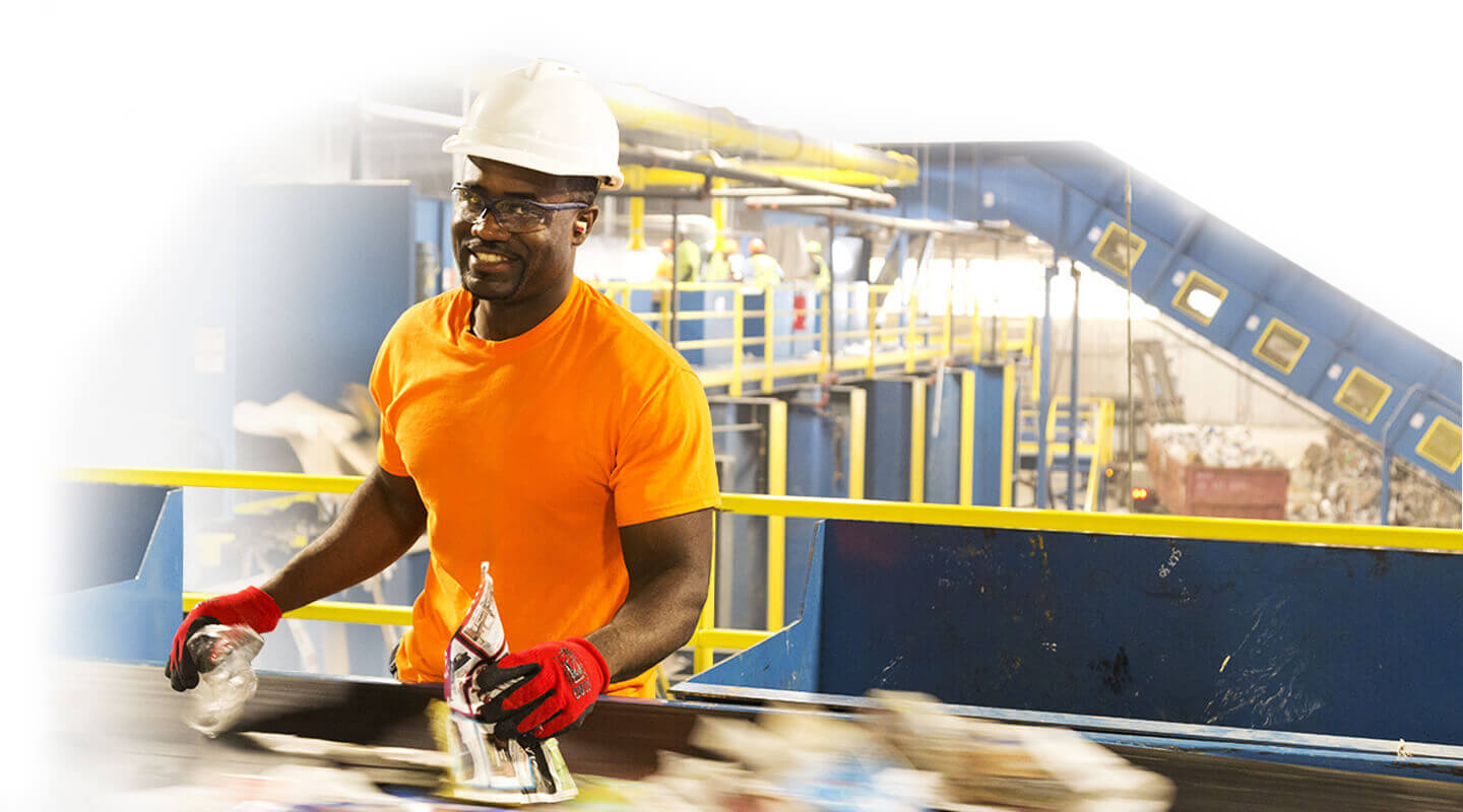 A man in an orange shirt working an a recycling plant.