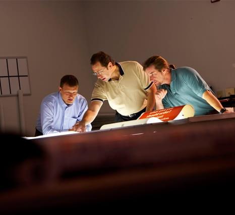 Três homens analisando um documento sobre a mesa
