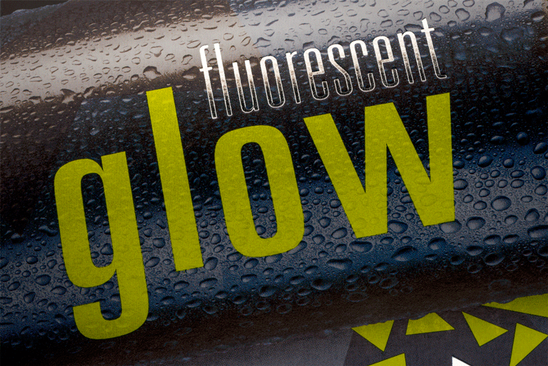 A close up of a black and yellow fluorescent glow beverage package.