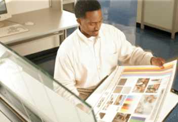 A man in an office looking at printing specifications on a large sheet of paper.