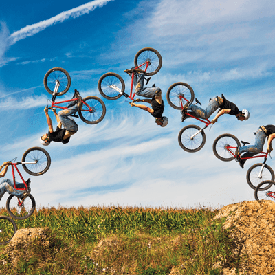 A time lapse photo of a bicycle rider performing a back flip trick.