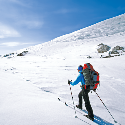 A man wearing skis hiking up a snowy mountain.