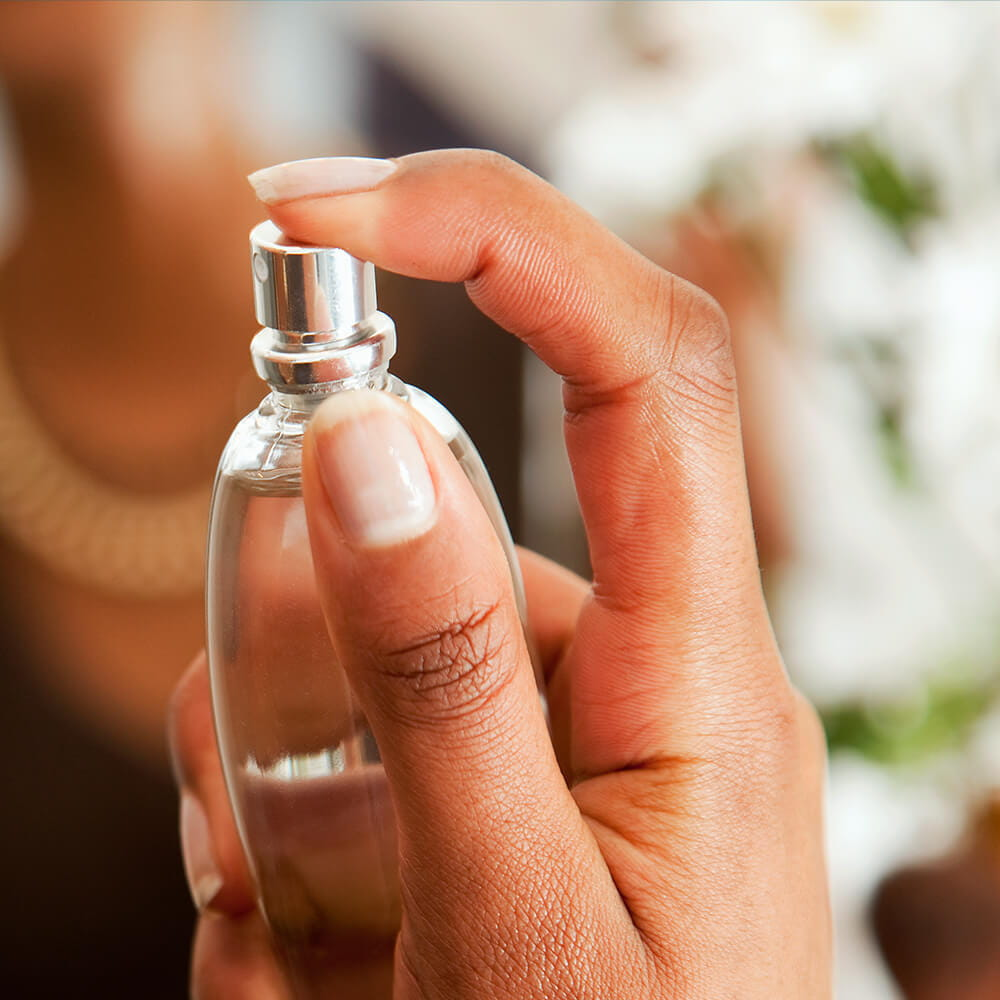 A woman holding up a perfume bottle with her hand.