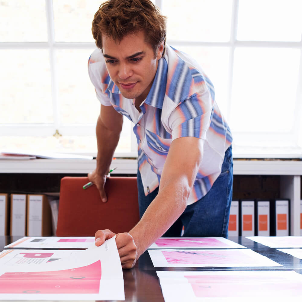 A man reviewing graphic design prints in an office.