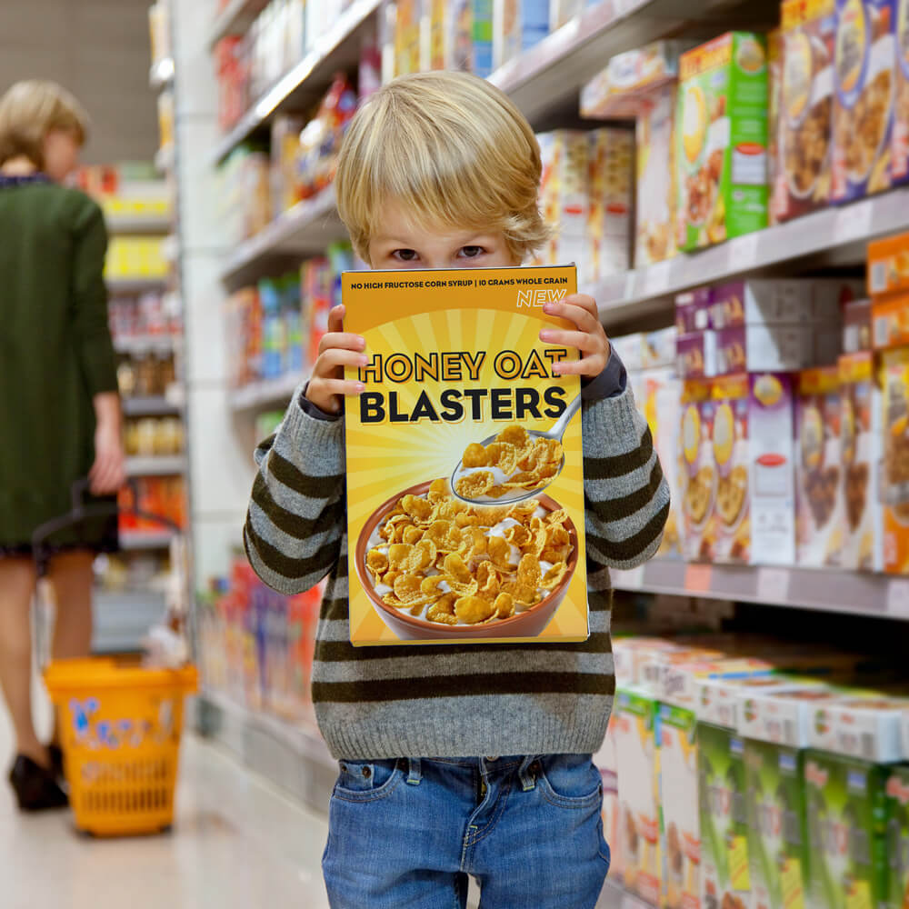 A little boy standing in a grocery store with a cereal box covering his face.