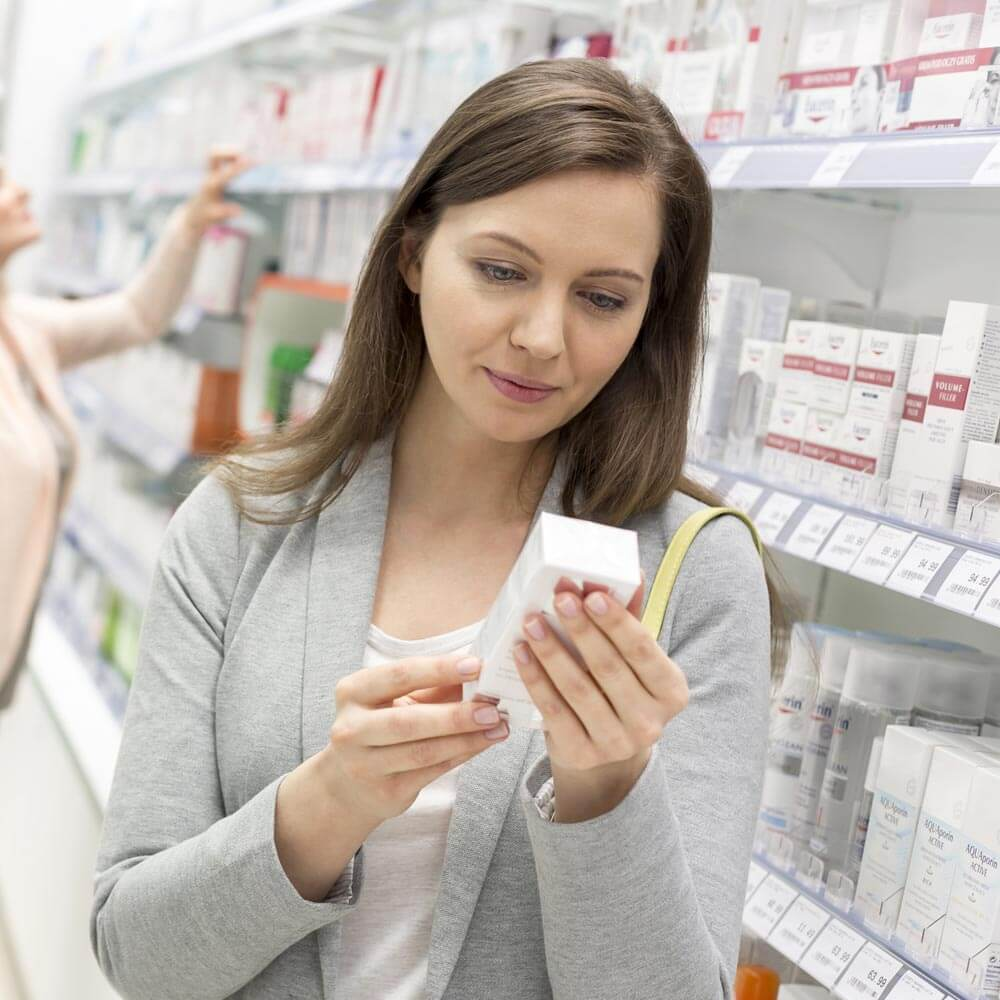 A woman shopping in pharmacy aisle of a retail store