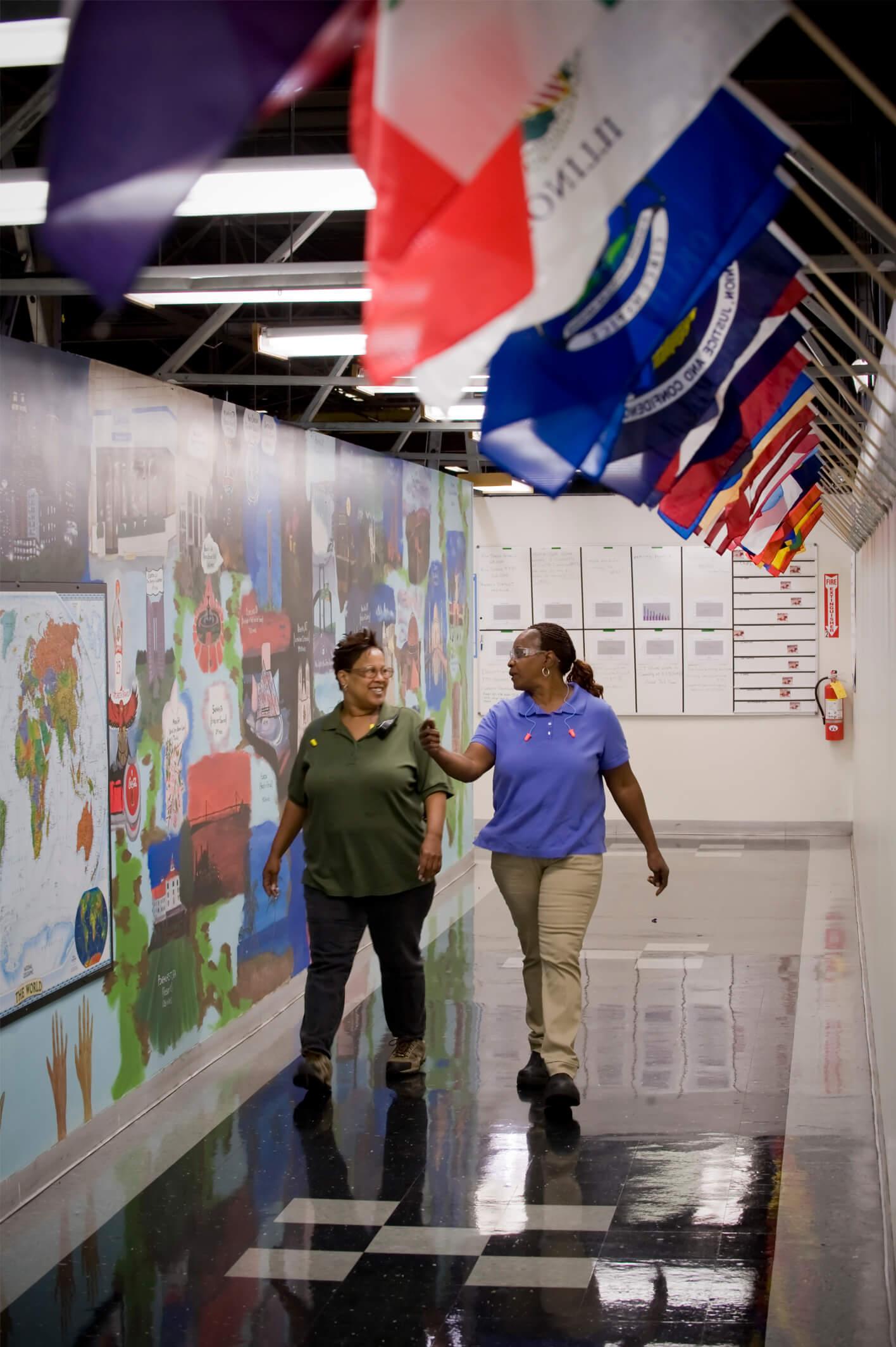 Duas mulheres andando por um corredor com bandeiras nacionais penduradas na parede.