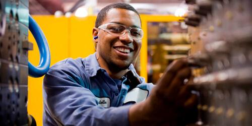Um eletricista trabalhando em uma máquina de fabricação.