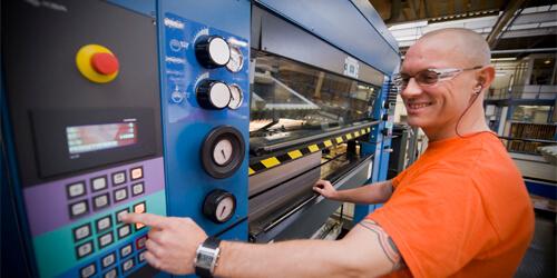 Um homem de camisa laranja preparando um maquinário para uso.