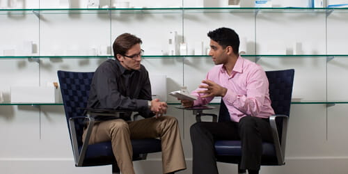 Dois homens sentados para uma reunião de vendas.