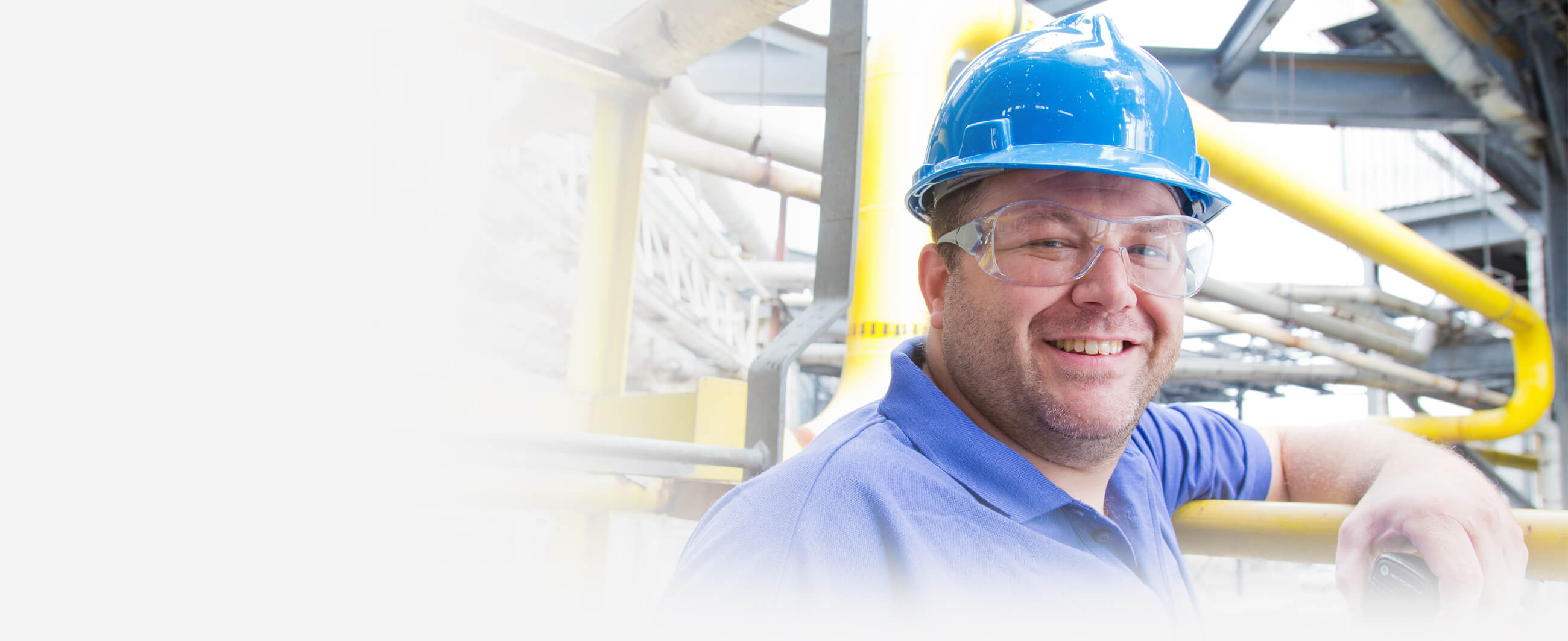 An employee in a blue hard hat and blue shirt.