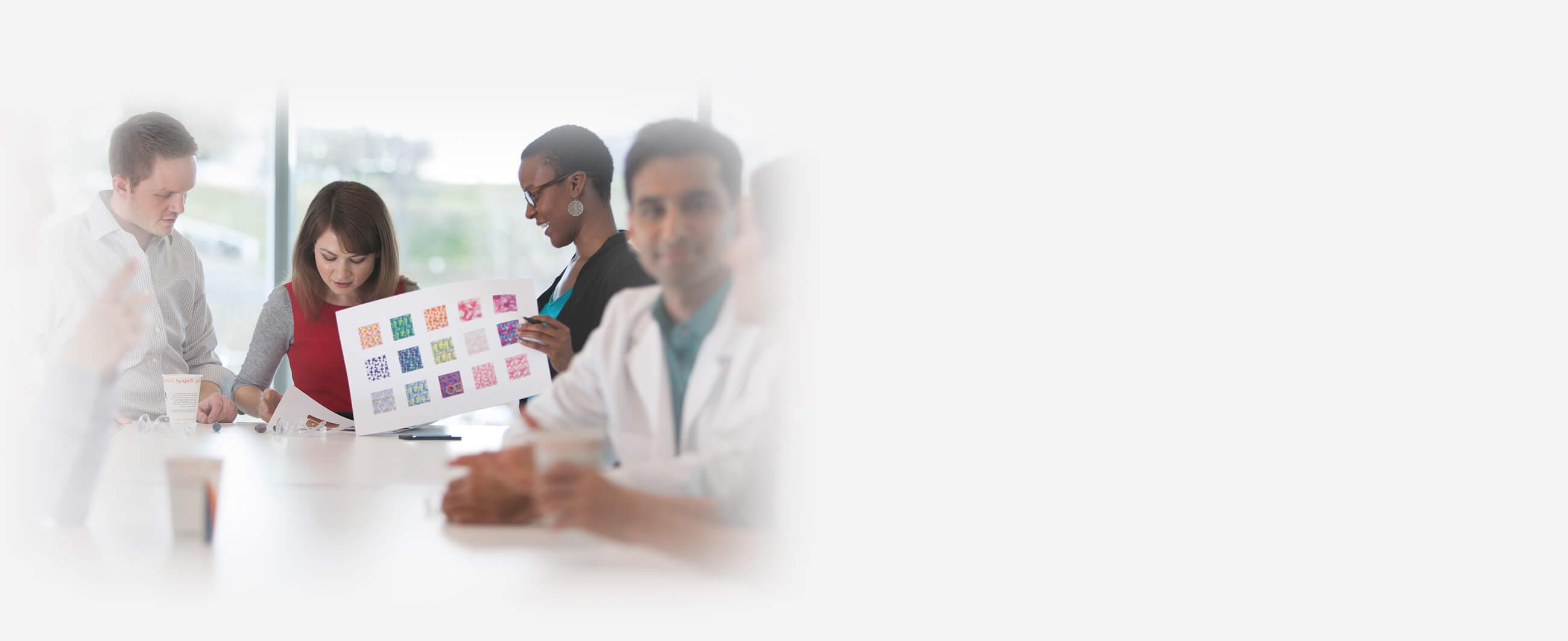 Um grupo de colegas de trabalho revisando um projeto em uma sala de reuniões.