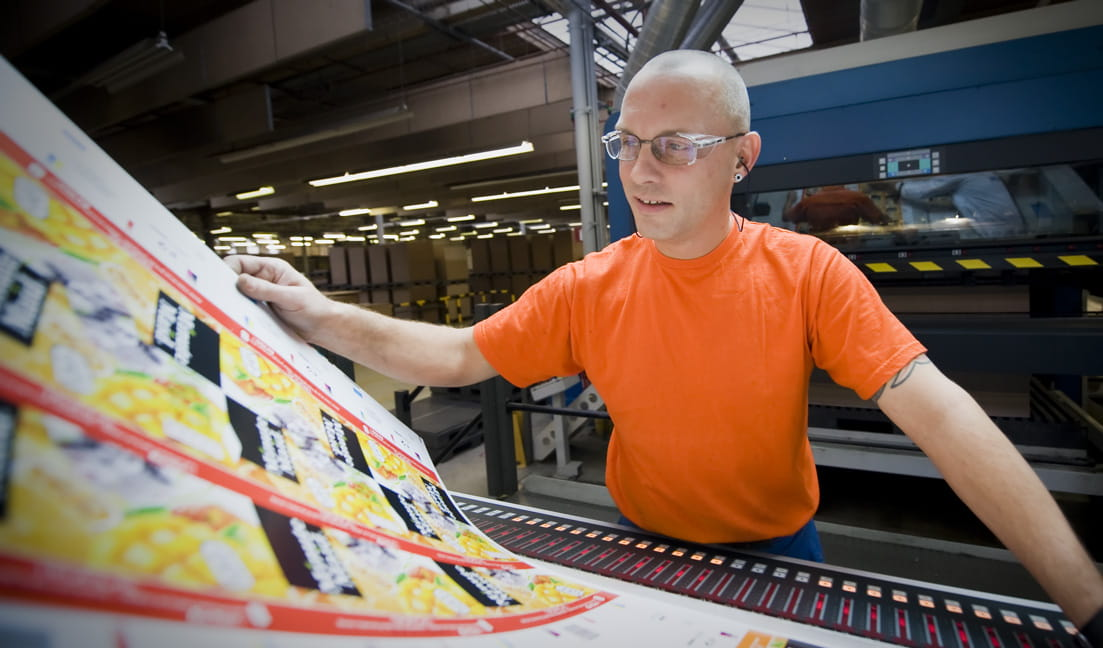 Um homem de camiseta laranja conferindo folhas de impressão comercial em um local de fabricação