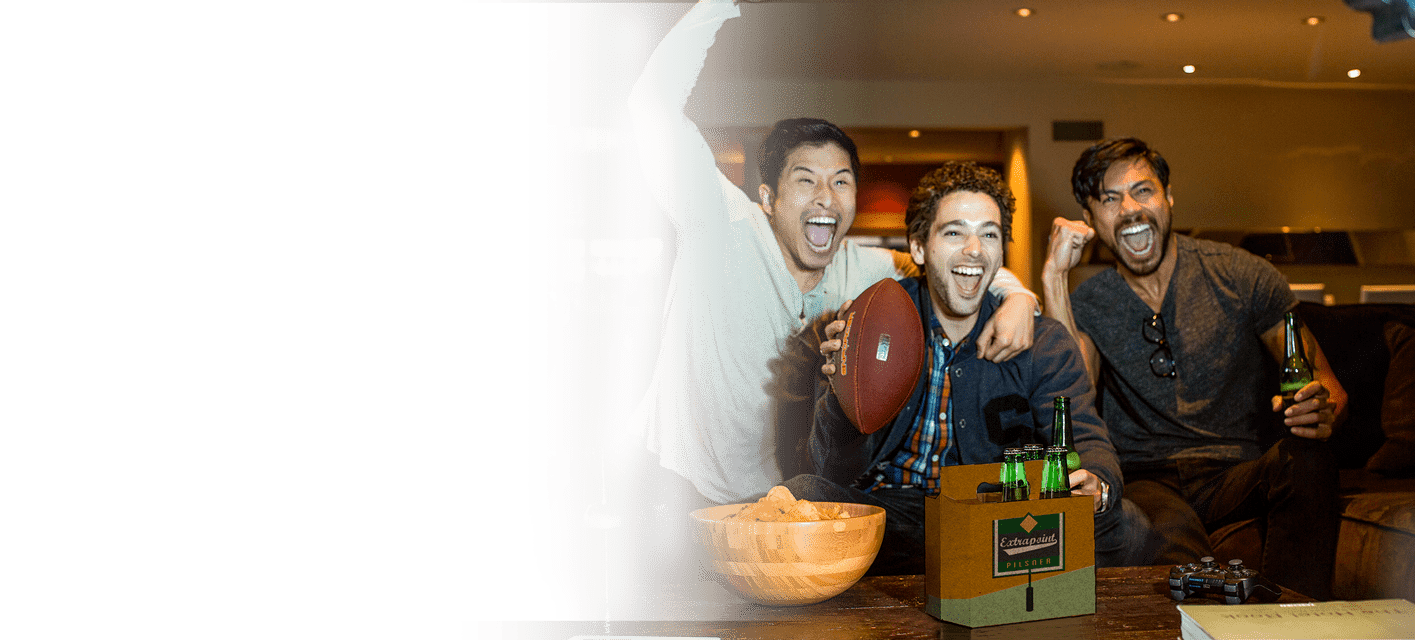 group of men watching football with six pack